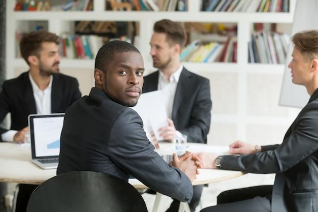 Uomo d'affari afroamericano sicuro che esamina macchina fotografica che si siede alla riunione
