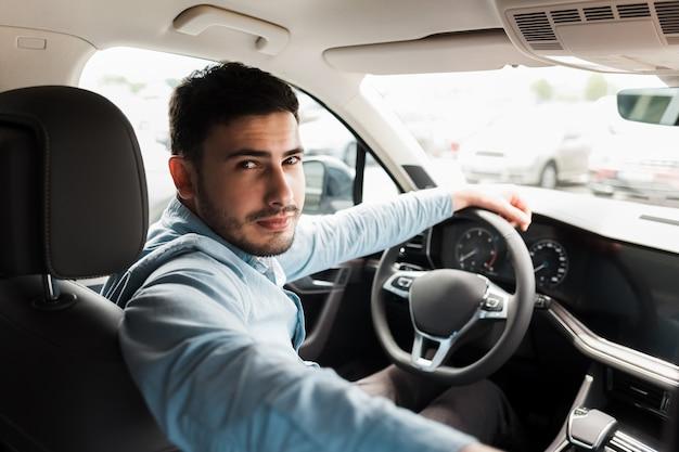 Uomo d'affari alla guida di un'auto di lusso