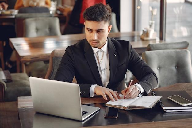 Uomo d'affari alla moda che lavora in un bar e utilizzare il computer portatile