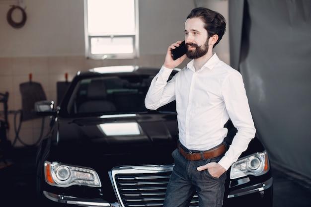 Uomo d'affari alla moda che lavora vicino all'automobile