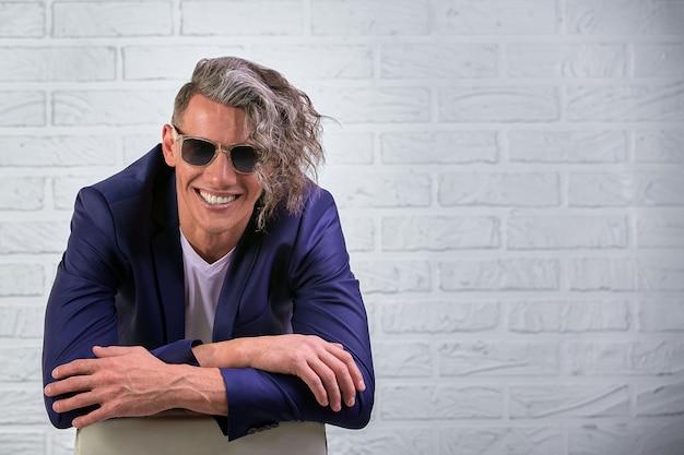 Uomo d'affari alla moda con capelli lunghi ricci in occhiali da sole che si siedono sulla sedia su bianco
