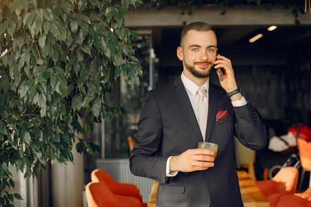 Uomo d'affari alla moda in un vestito nero che lavora in un caffè