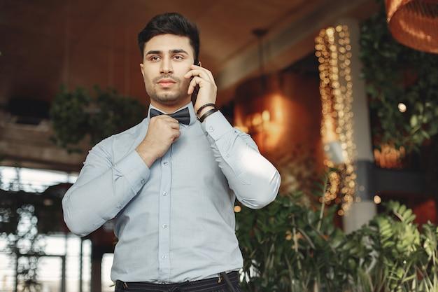 Uomo d'affari alla moda in una camicia blu che sta dell'interno