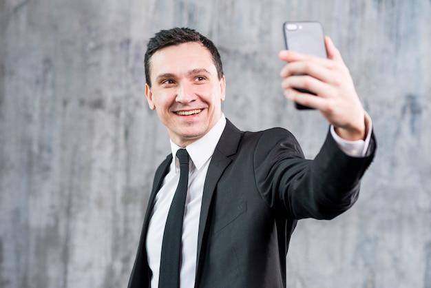 Uomo d'affari alla moda sorridente che prende selfie con lo smartphone