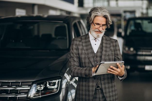 Uomo d'affari alla ricerca di un'auto in un salone di auto