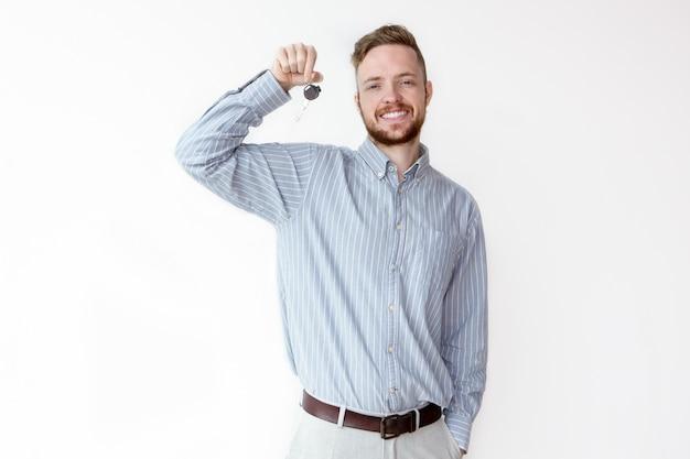 Uomo d'affari allegro che dà chiave auto o appartamento