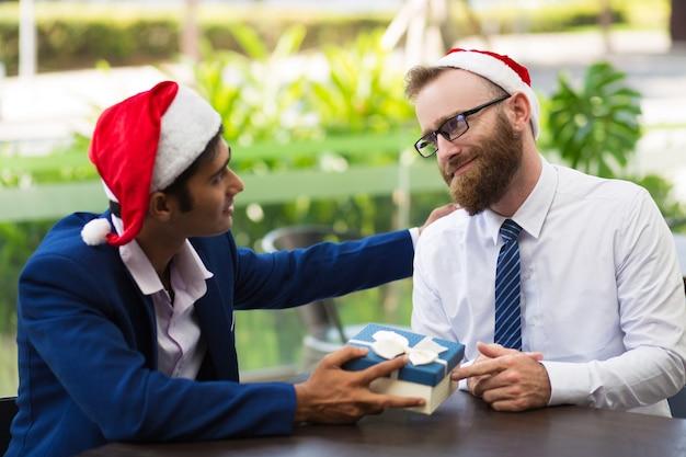 Uomo d'affari allegro che dà il contenitore di regalo al collega