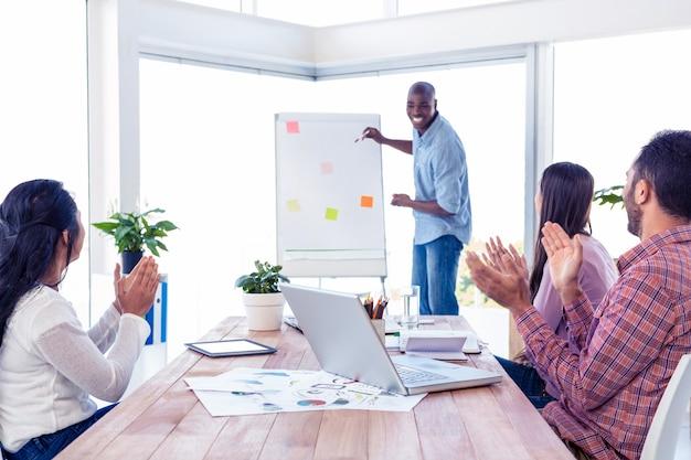 Uomo d'affari allegro che dà presentazione mentre squadra che applaude in ufficio creativo