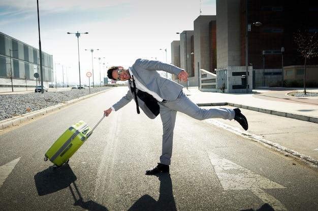 Uomo d'affari allegro che gioca con la sua valigia