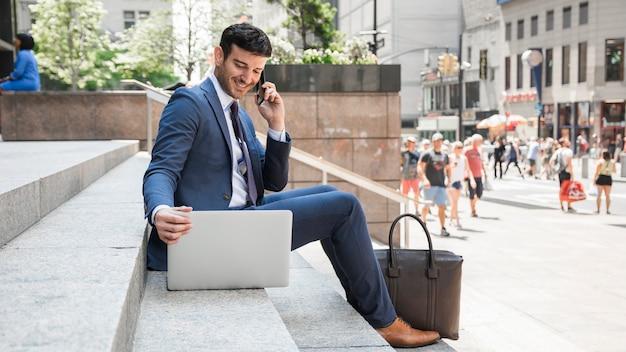 Uomo d'affari allegro che parla sul telefono e che per mezzo del computer portatile