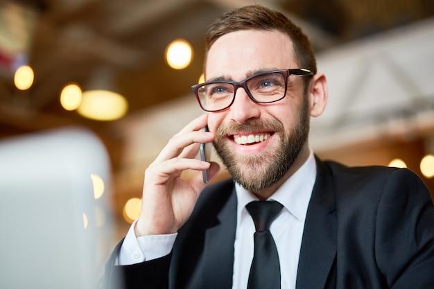 Uomo d'affari allegro che per mezzo dello smartphone
