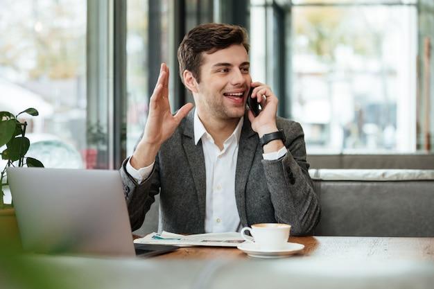 Uomo d'affari allegro che si siede dalla tavola in caffè con il computer portatile e che parla dallo smartphone mentre ondeggiando e distogliendo lo sguardo