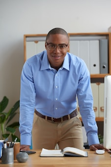 Uomo d'affari allegro che sta nell'ufficio che si appoggia lo scrittorio e che sorride alla macchina fotografica