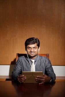 Uomo d'affari allegro con computer tablet