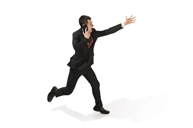 Uomo d'affari allegro divertente che corre e che parla sul telefono