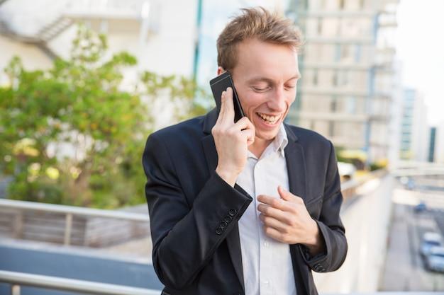 Uomo d'affari allegro eccitato in chat sul telefono