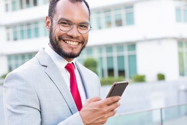 Uomo d'affari allegro felice con gli smartphones che posano all'aperto