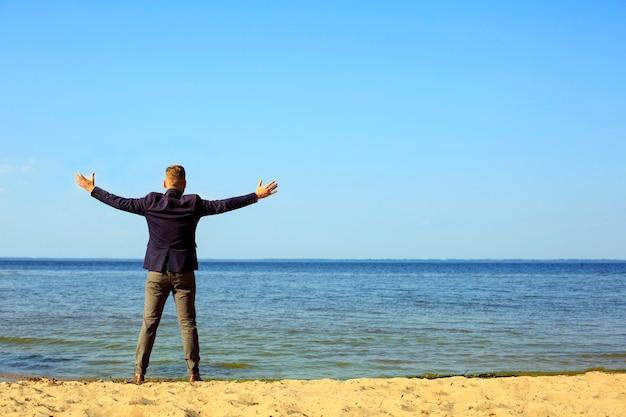 Uomo d'affari alzando le braccia, le palme aperte, con la faccia alzando lo sguardo verso il cielo