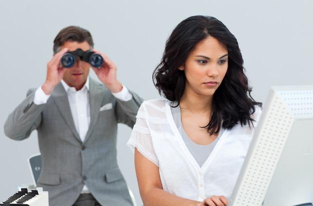 Uomo d'affari ambizioso che guarda il suo computer del collega tramite il binocolo