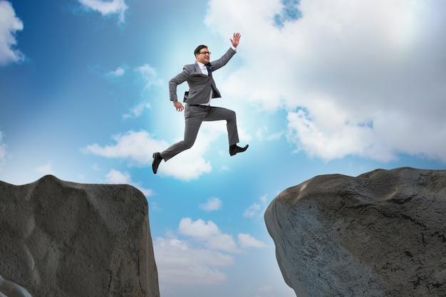 Uomo d'affari ambizioso che salta sopra la scogliera