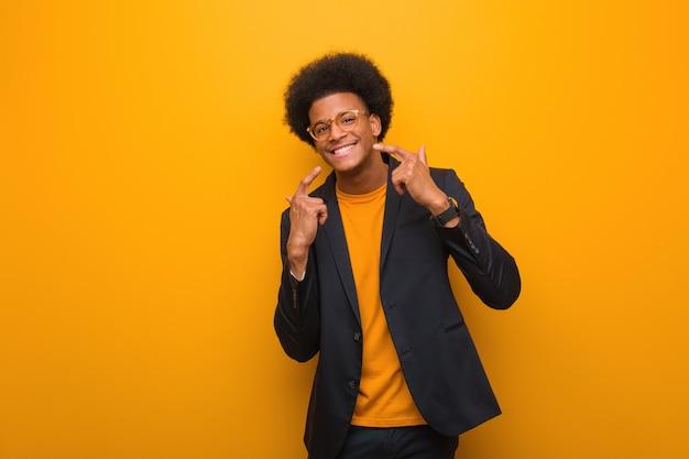 Uomo d'affari americano africano giovane sopra un muro arancione sorride, indicando la bocca