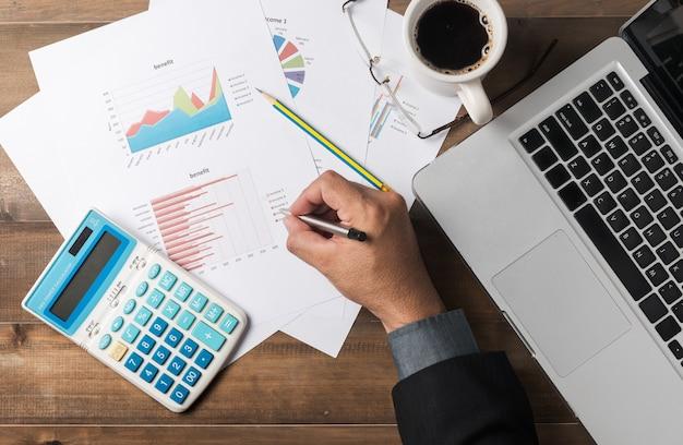 Uomo d'affari analizzando grafici e prendendo appunti
