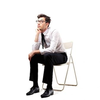 Uomo d'affari annoiato che si siede su una sedia