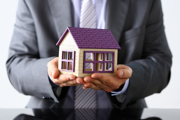 Uomo d'affari anziano che dimostra il modello della casa