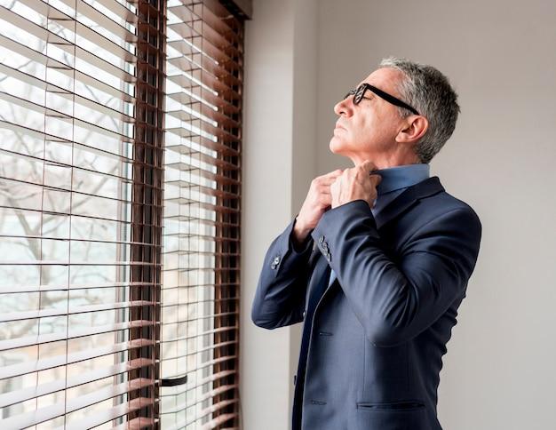 Uomo d'affari anziano che osserva attraverso la finestra