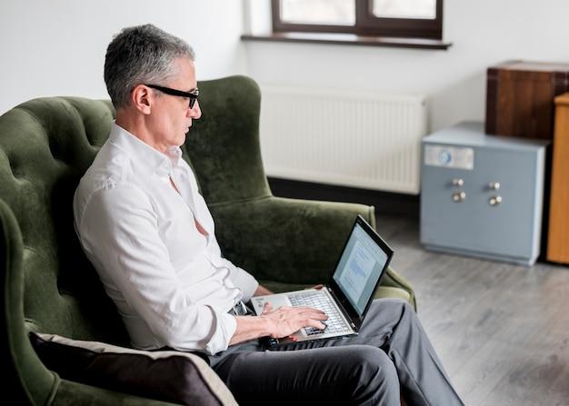 Uomo d'affari anziano che per mezzo del computer portatile su una poltrona