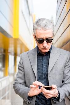 Uomo d'affari anziano che per mezzo del telefono cellulare