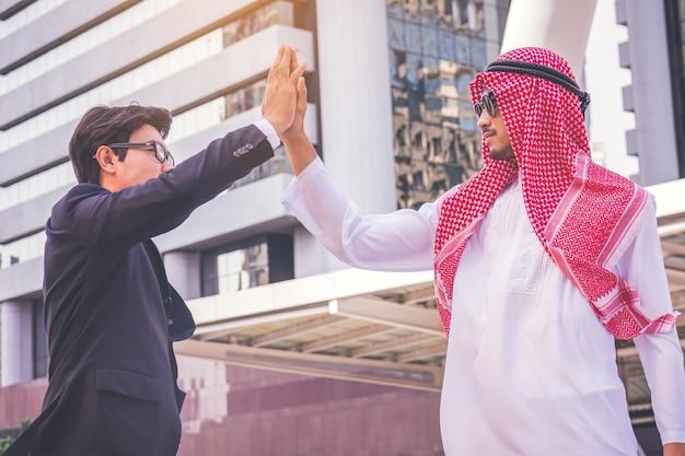 Uomo d'affari arabo che dà il livello cinque al suo socio commerciale, sul cantiere
