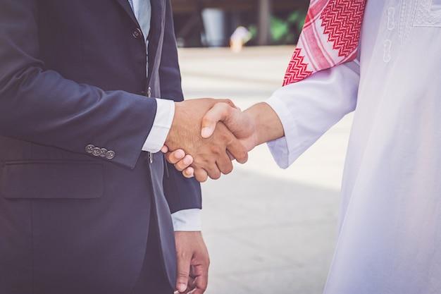 Uomo d'affari arabo che dà una stretta di mano al suo socio commerciale, sul cantiere