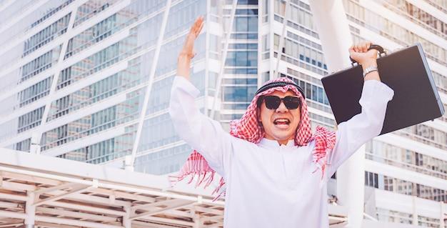 Uomo d'affari arabo che fa una pausa alzando entrambe le mani in su in città