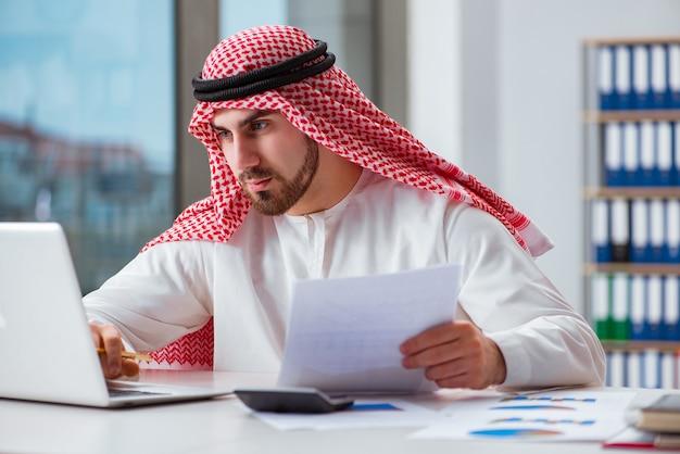 Uomo d'affari arabo che lavora al computer portatile