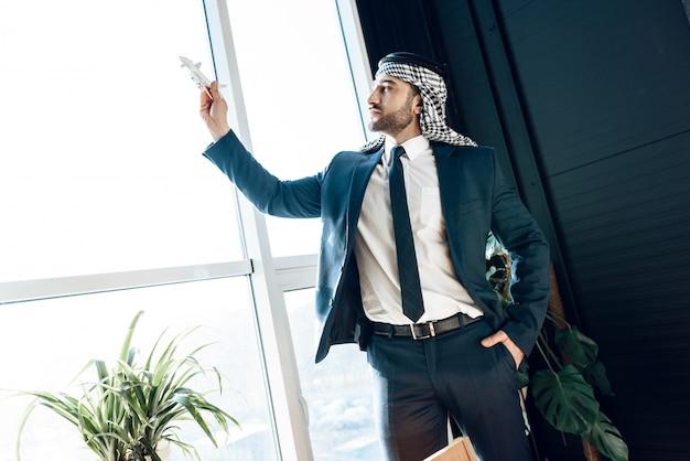Uomo d'affari arabo che sta alla finestra con l'aeroplano di modello.