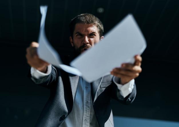 Uomo d'affari arrabbiato che tiene i documenti