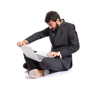 Uomo d'affari arrabbiato con il computer portatile su sfondo bianco