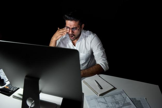 Uomo d'affari asiatico affaticato che ritiene assonnato e che sbadiglia mentre lavorando il turno di notte