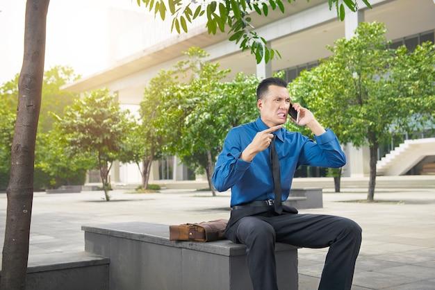 Uomo d'affari asiatico arrabbiato mentre parlando sul suo cellulare