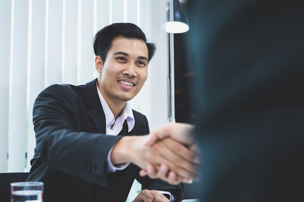 Uomo d'affari asiatico che agita le mani dopo la chiusura dell'affare