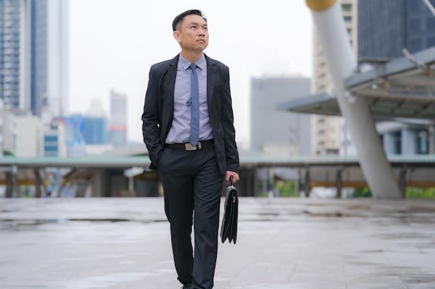 Uomo d'affari asiatico che cammina e che tiene cartella con gli edifici per uffici di affari nella città