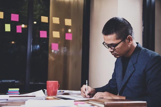 Uomo d'affari asiatico che controlla dati e che funziona alla notte