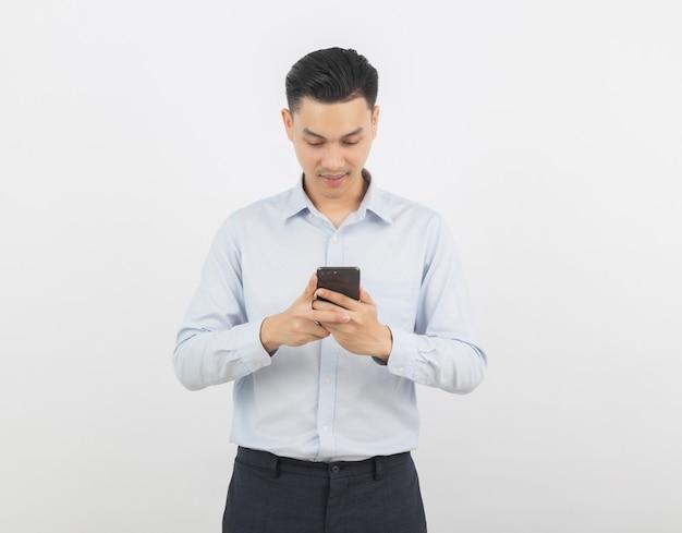 Uomo d'affari asiatico che gioca smartphone con sorridere isolato su priorità bassa bianca
