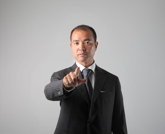 Uomo d'affari asiatico che indica la macchina fotografica
