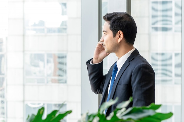 Uomo d'affari asiatico che invita telefono cellulare