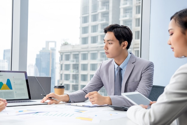 Uomo d'affari asiatico che presenta il grafico di dati nella riunione