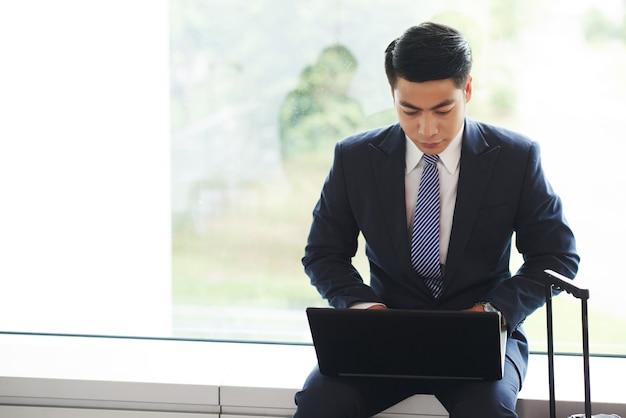 Uomo d'affari asiatico che si siede sul davanzale, con la rappresentazione della maniglia della valigia e che lavora al computer portatile