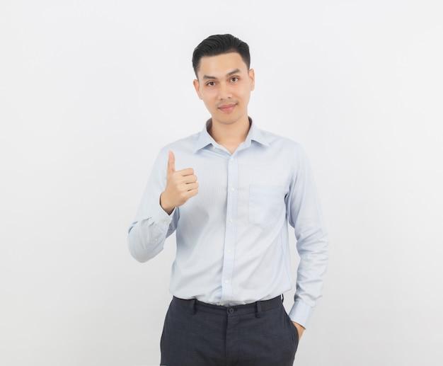 Uomo d'affari asiatico che sorride e che mostra i pollici in su isolati su priorità bassa bianca