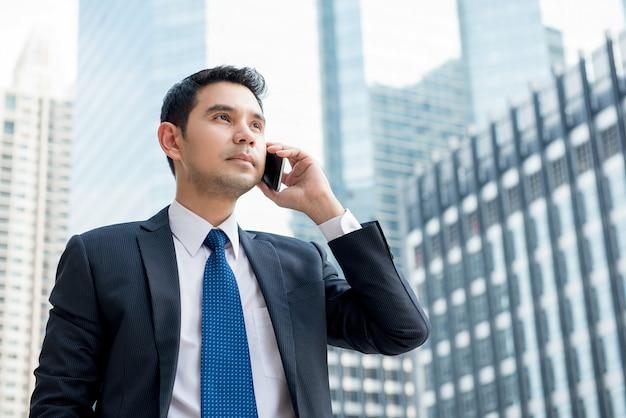 Uomo d'affari asiatico che sta all'aperto che rivolge al telefono cellulare nel distretto aziendale centrale